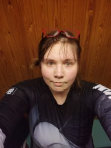 A round-faced human with glasses raised to their forehaed. Looks at camera, dressed in a grayscale rash guard.