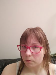 Person with red-rimmed glasses and red cheecks, staring at camera in a pyjama.