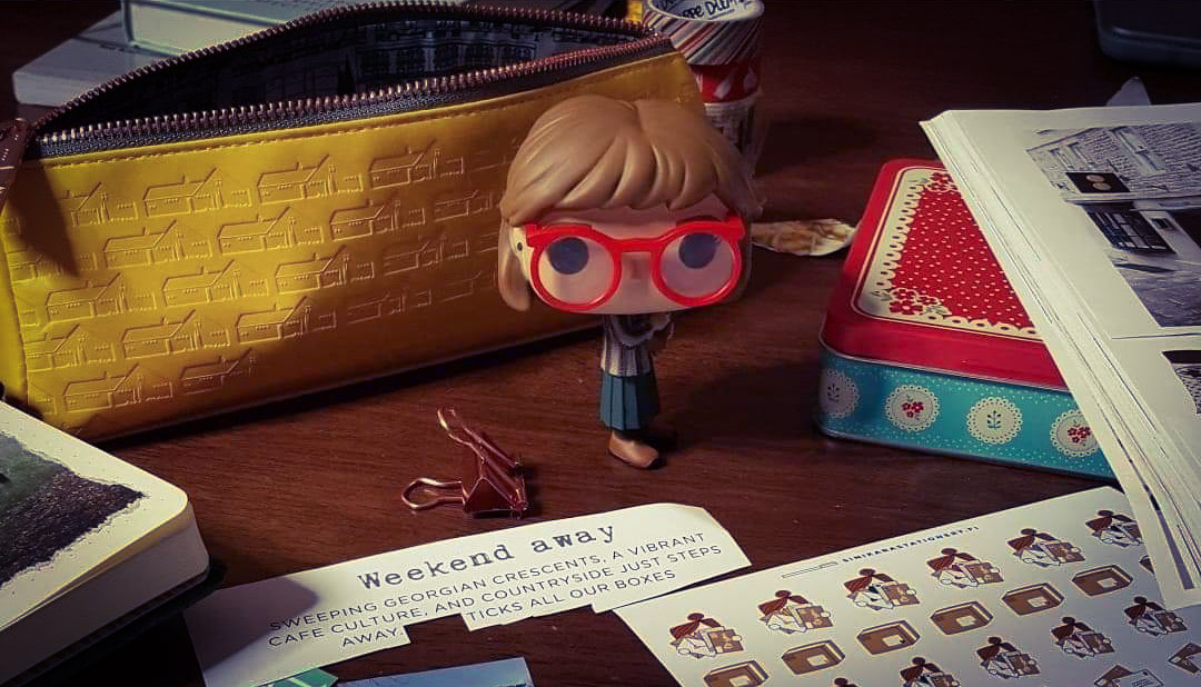 Doll on table with brown hair and red glasses.