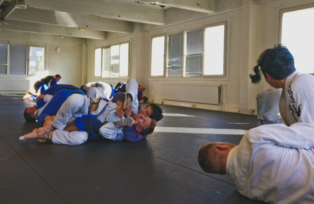 People grappling in a gym.
